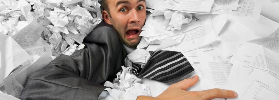 man snowed under paperwork