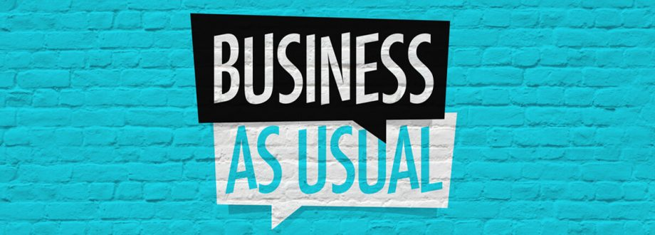 business as usual sign on a blue brick wall