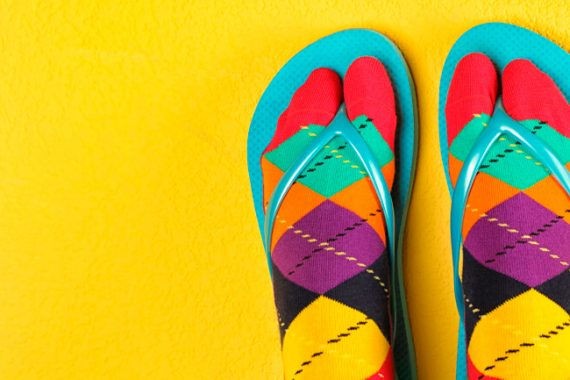 colourful bad taste socks and flip flops on yellow background